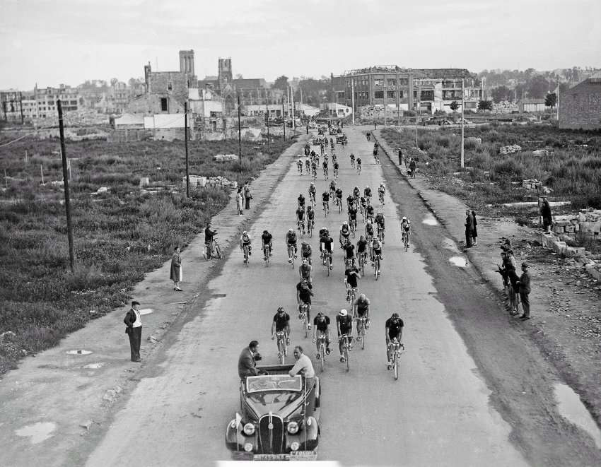 1947: The Tour de France resumed two years after the World War II. In the photo above, you can see the riders leaving the town of Caen. Damage to the buildings is still visible.