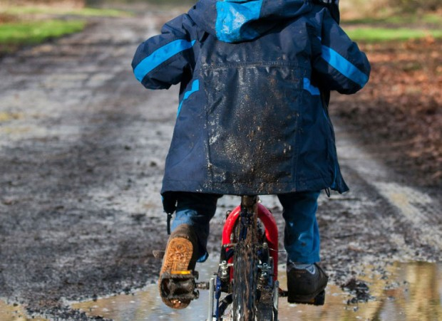 Little boy riding in mud on a bicycle
