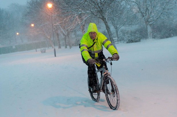 Riding a bicycle in winter in high visibility jacket