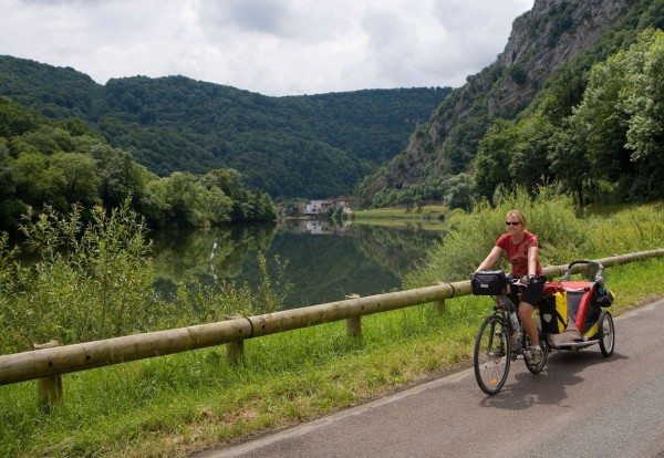 Cyclist on the towpath along the Doubs River, EuroVelo 6 bike route