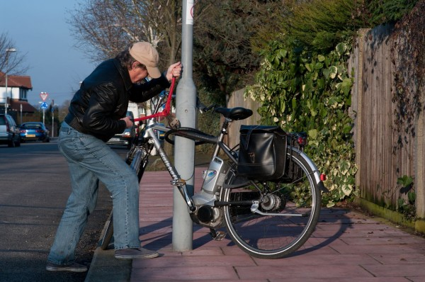 Bicycle thief takes wire cutters to steal chained up bike.